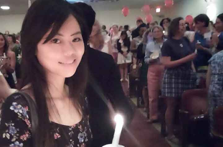 Anh Luong holding candle during Alumnae Weekend ceremony
