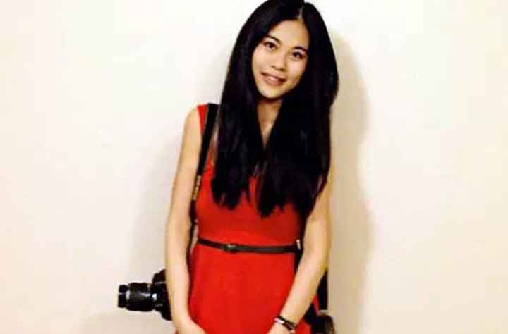 Ronnie Deng poses for the camera with her own camera in hand