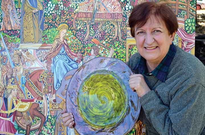 Elizabeth Bailey holding her award in front of her artwork