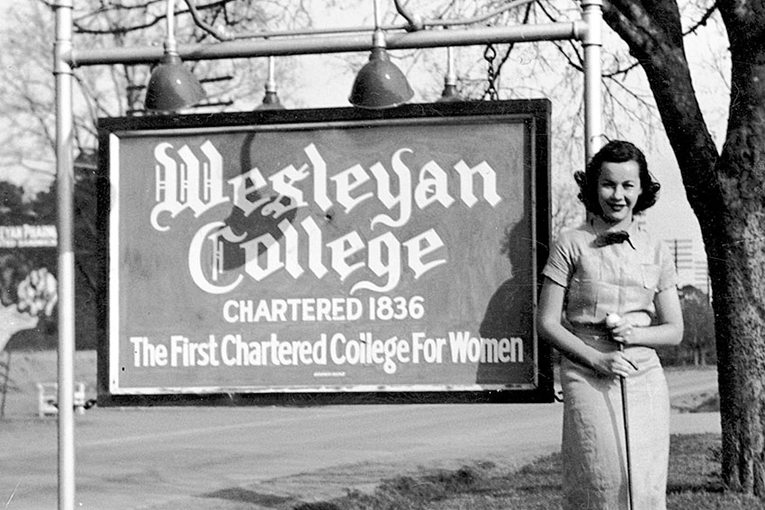 Wesleyan students stands next to Wesleyan sign that says chartered in 1836.