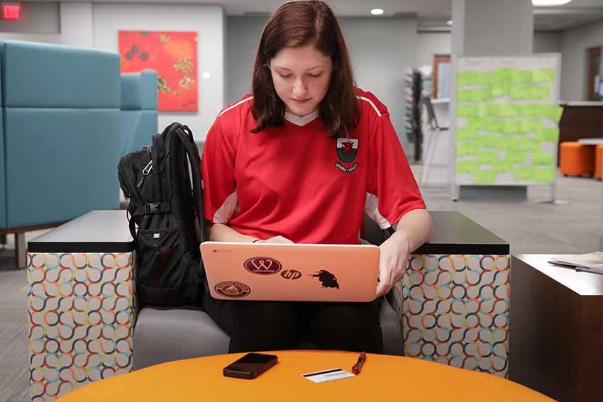 Student in studying in Willet Library on her laptop.