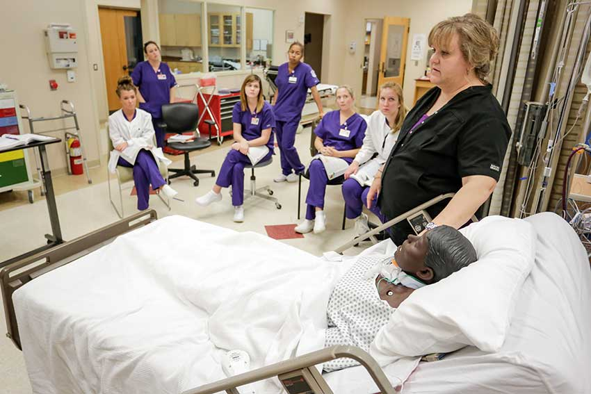 Students listing in Nursing lab as teacher talks.