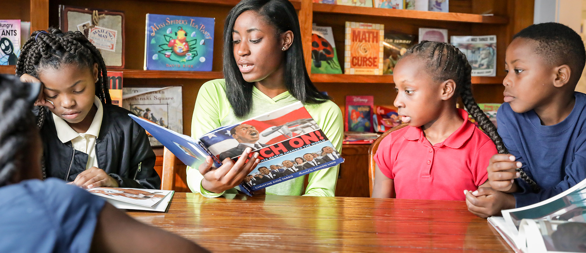 Wesleyan student reads to children through Aunt Maggies Kitchen program.