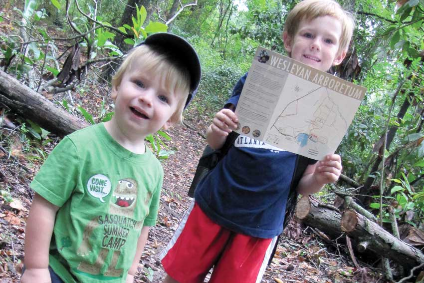 Two boys hiking in the arboretum holding up the map