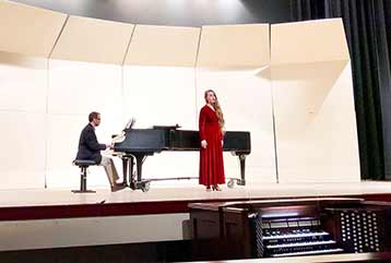 Student on Porter Stage singing in red gown