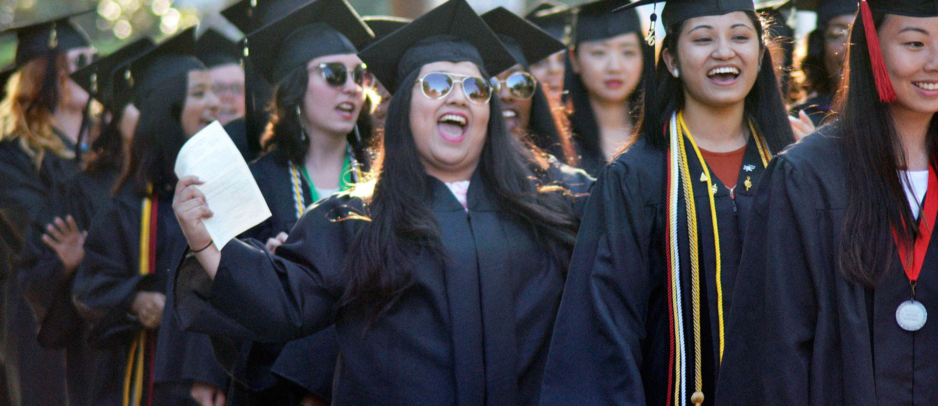 Students cheer in graduation gowns while walking to the church in downtown macon