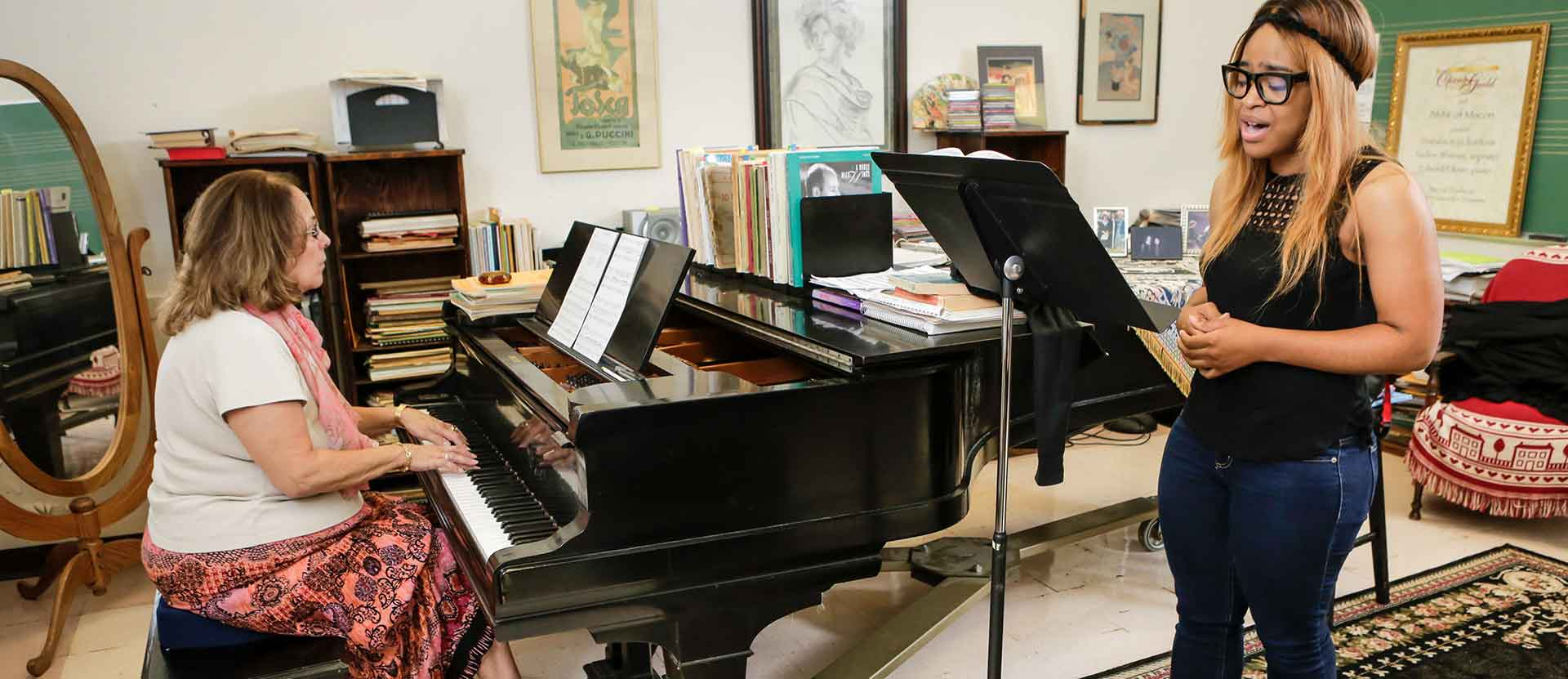 Music student practices singing with professor during her office hours