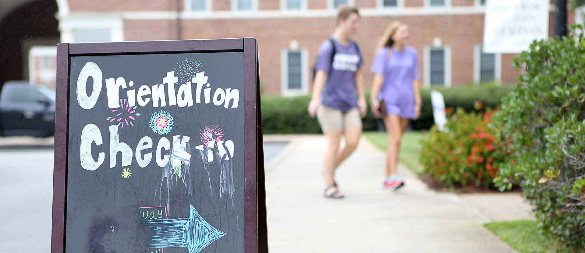 Students walk in the background with a sign for Student Orientation in the foreground.