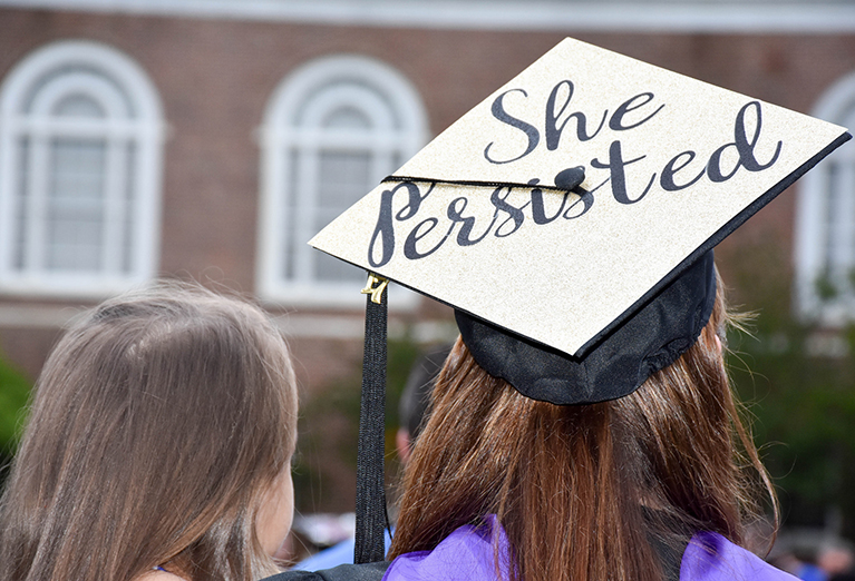 Photo of student with cap that says she persisted