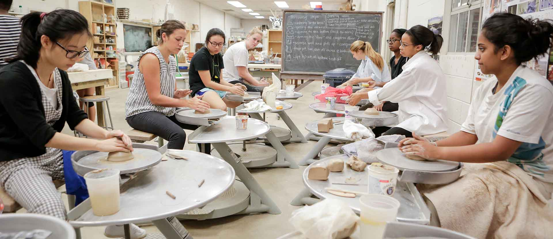 Studio art students create bowls on pottery wheel