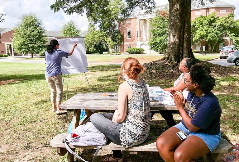 Students studying outside on the picnic table.