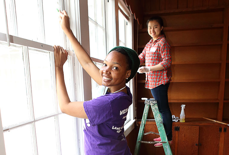 Two students paint window sill